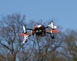 SQ1 mini quadcoper flying against spring treetops and blue sky